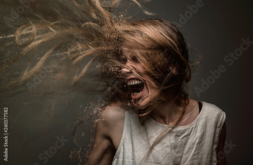 Fotografiet  Screaming crazy frustrated woman dispersing into million particles, anxiety, ang