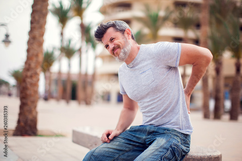 Fotomural  Man with back pain sitting on bench at the outdoor