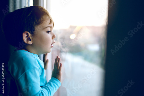 Fototapeta Little boy at home looking trough the window waiting for his mother parents to c