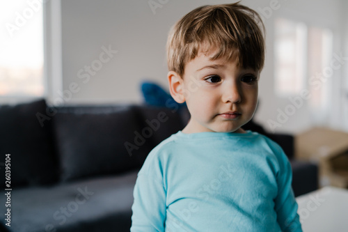 Obraz na plátně Portrait of a little boy in blue at home standing in the middle of the room