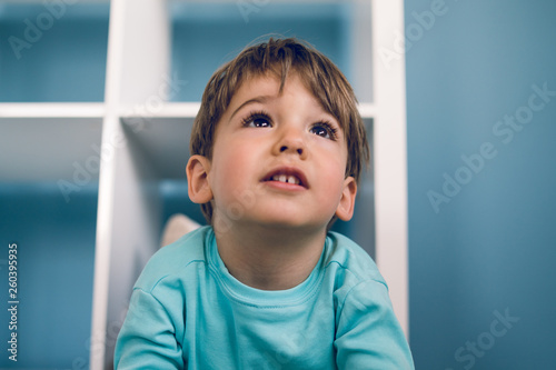 Fotografie, Obraz Portrait of a little boy in blue at home lying in the book shelf on the floor hi