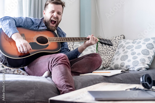 Fotografía  A young, handsome male composer plays an acoustic guitar and loudly sings a song of his own composition, sitting on a sofa, in a comfortable home environment with natural light