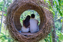 Asian Woman And Man Enjoying His Time Sitting On A Bird Nest In The Tropical Jungle Near The Rice Terraces In Island Bali, Indonesia