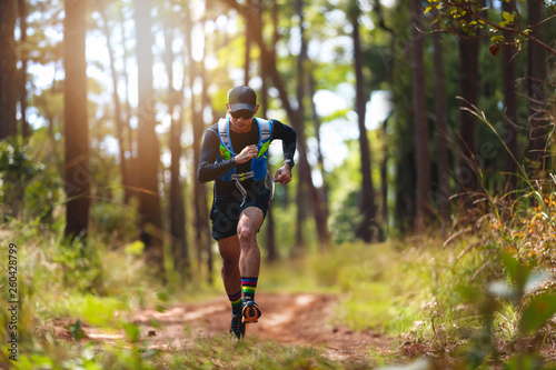 A man Runner of Trail . and athlete's feet wearing sports shoes for trail running in the forest - 260428799