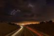 Ein Gewitter mit Blitzen und dramatischen Wolken in der Nacht über der Autobahn