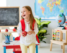 Little Laughing Blond Girl Holding An Apple In The School Classroom