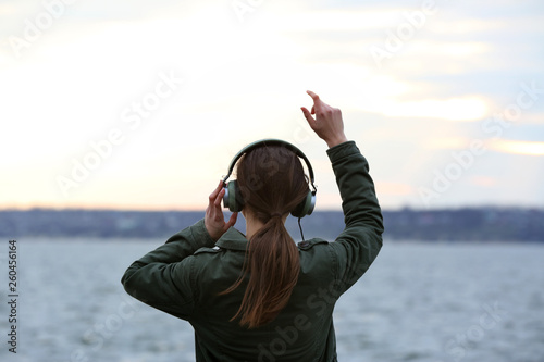 Fototapety, obrazy: Young woman listening to music near river