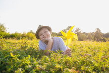 Closeup Portrait Of White Happy Smiling Little Kid Laying On Green Grass In Meadow Outdoors Holding Yellow  Pinwheel In Hand. Happy Summer Moments Concept.