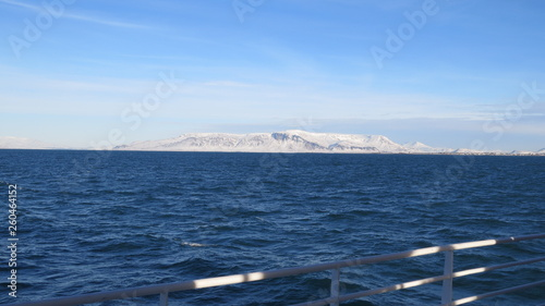 Fotografie, Obraz  Atlantik um Reykjavik und schneebedeckte Hügel mit blauem Himmel und Geländer im