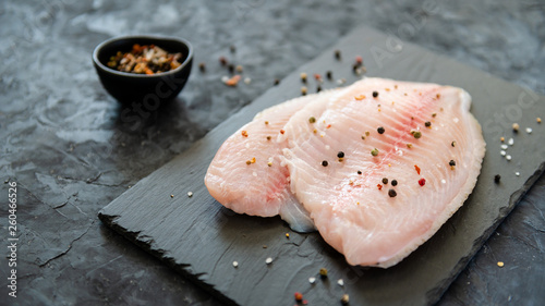 Tablou Canvas fresh fish fillet with ingredients for cooking on stone plate on dark background