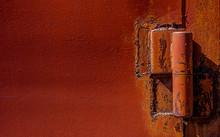 Red Painted Door Hinge Welded On Red Metal. Horizontal Steel Texture