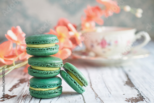 Stack of fresh french green tea macarons on a white rustic table with flowers and antique tea cup blurred in background..