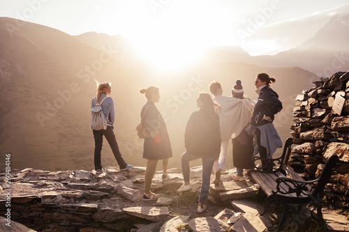 Foto auf Leinwand Lachs Group of beautiful stylish motivated young people posing on top of a mountain in the sun rays of sunset. Concept of hiking trip and community, female friendship and support and unity with nature