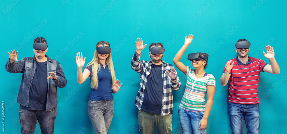 Fototapeta Group of friends using new technology playing on vr glasses indoor – virtual reality with people having fun together
