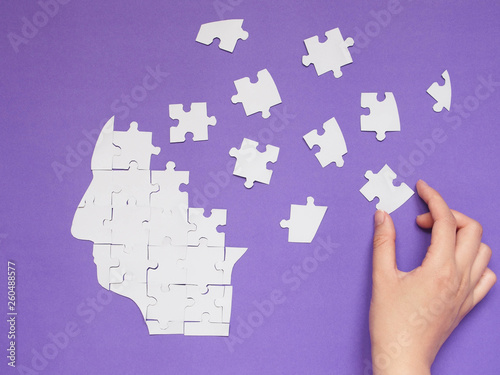 Female hand trying to connect pieces of white jigsaw puzzle as a human head brain on purple background Canvas Print