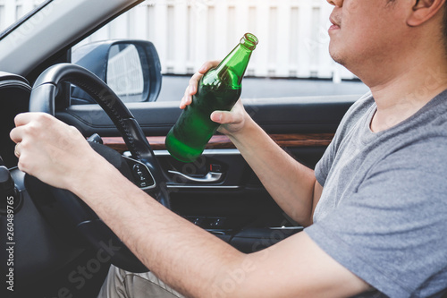 Fotografie, Tablou Young asian man drives a car with drunk a bottle of beer behind the wheel of a c
