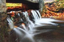 Small Waterfall On A Creek Autumn Landscape In A Park Water