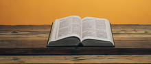 Open Holy Bible On A Old Oak Wooden Table. Orange Wall Background..