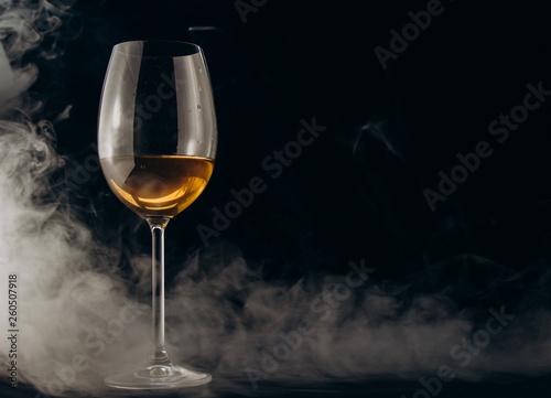 Fotografía  a glass of white wine on a black background