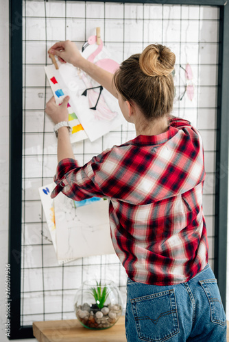 Vászonkép Back view of teenager in checkered shirt hanging drawing on pinboard