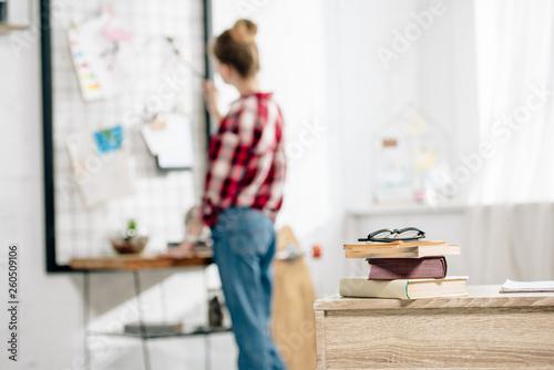 Selective focus on teenager in jeans looking at pinboard Tapéta, Fotótapéta
