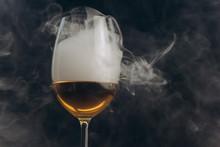 A Glass Of White Wine On A Bla...