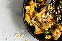 Roasted Cauliflower With Spinach, Raisin And Nuts In A Cast-iron Pan. Light Grey Background. Copy Space. Healthy Vegan Food.
