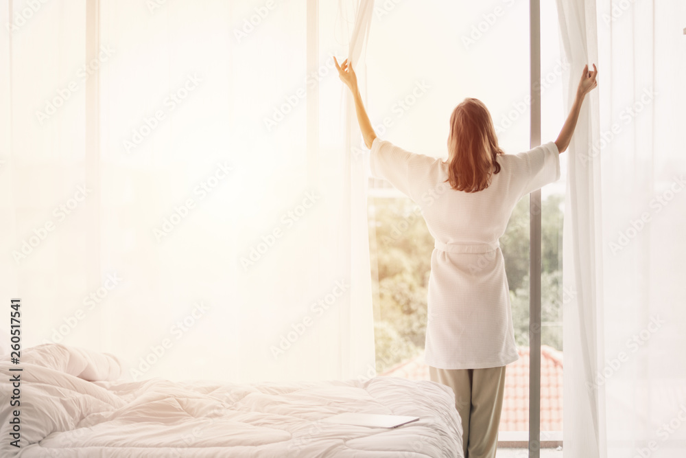 Fototapety, obrazy: view back woman opening curtains in a white bedroom