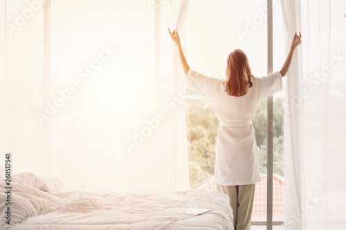 view back woman opening curtains in a white bedroom