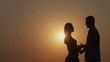 Silhouettes of a couple in love opposite a warm sunset