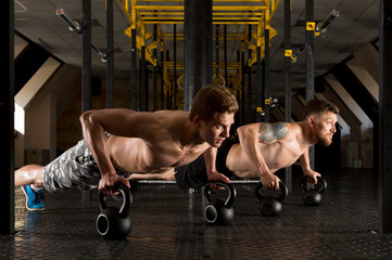 Fototapeta Fitness / Siłownia Muscular men doing pushups on kettleball in gym