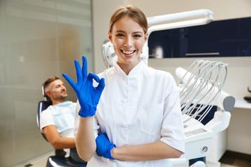 Piękna szczęśliwa młodej kobiety lekarka w medycznym dentysty centrum pokazuje zadowalającego gest.
