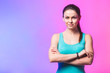 Happy fitness woman standing with arms folded over white background and looking at camera.