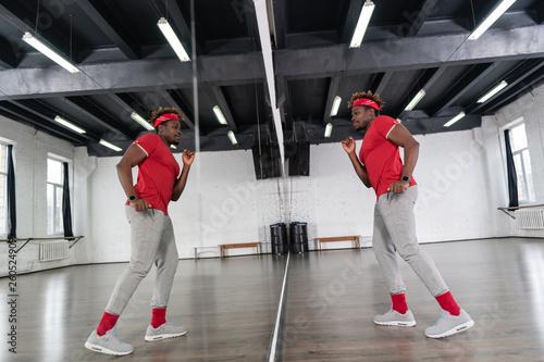 Fotografía  Artistic dark-skinned man posing in front of full length mirror