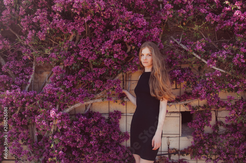 Portrait of girl among purple bougainvillaea Poster Mural XXL