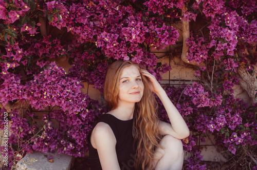 Photo Portrait of smiling girl among purple bougainvillaea