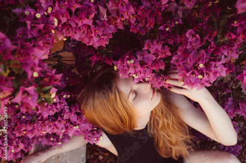 Canvas Print Portrait of girl with closed eyesamong purple bougainvillaea