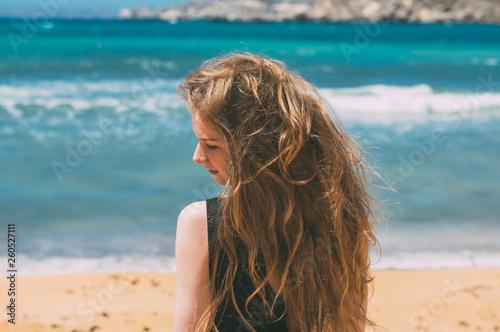 Fotografia  Portrait of girl in black dress on windy beach