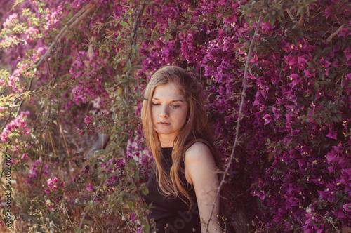 Canvas Portrait of girl among purple bougainvillaea