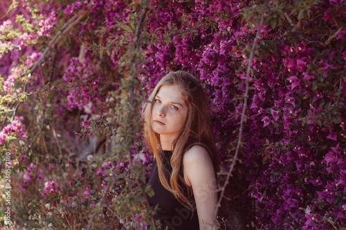 Portrait of girl among purple bougainvillaea Fototapete