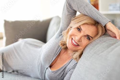 Attraktive Frau liegt zuhause auf der Couch Wallpaper Mural