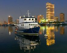 Night Scenery Of A Ship Docking At Manila Bay Near Manila Yacht Club With Illuminated High-rise Buildings In The Background Reflecting In The Water