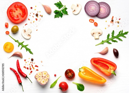 Foto Organic fresh vegetables and spices frame on wooden white background