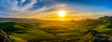 Panorama Of Setting Sun On Rolling Green Hills