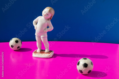 porcelain statuette of boy doing warming up exercises and two footballs on brigh Wallpaper Mural