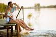 Leinwandbild Motiv Loving couple sitting on the pier on lake