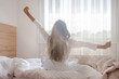 canvas print picture - Young woman waking up in her bedroom, sitting on the bed stretching arms by the window
