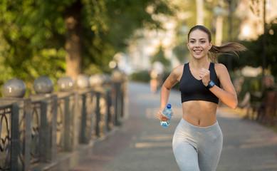 Happy sporty millennial woman running on quay