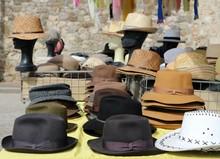 Different Style Men Hats On A Shelf Of A Street Market. On Background, Manikin Heads Wearing Straw Hats