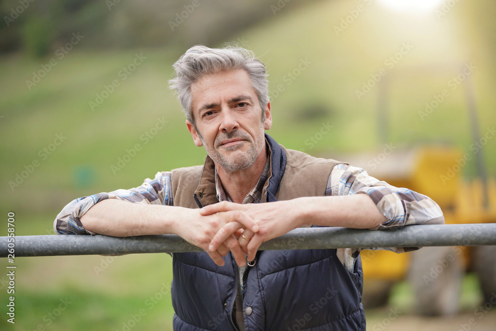 Fotografía  Attractive farmer leaning on fence looking at camera